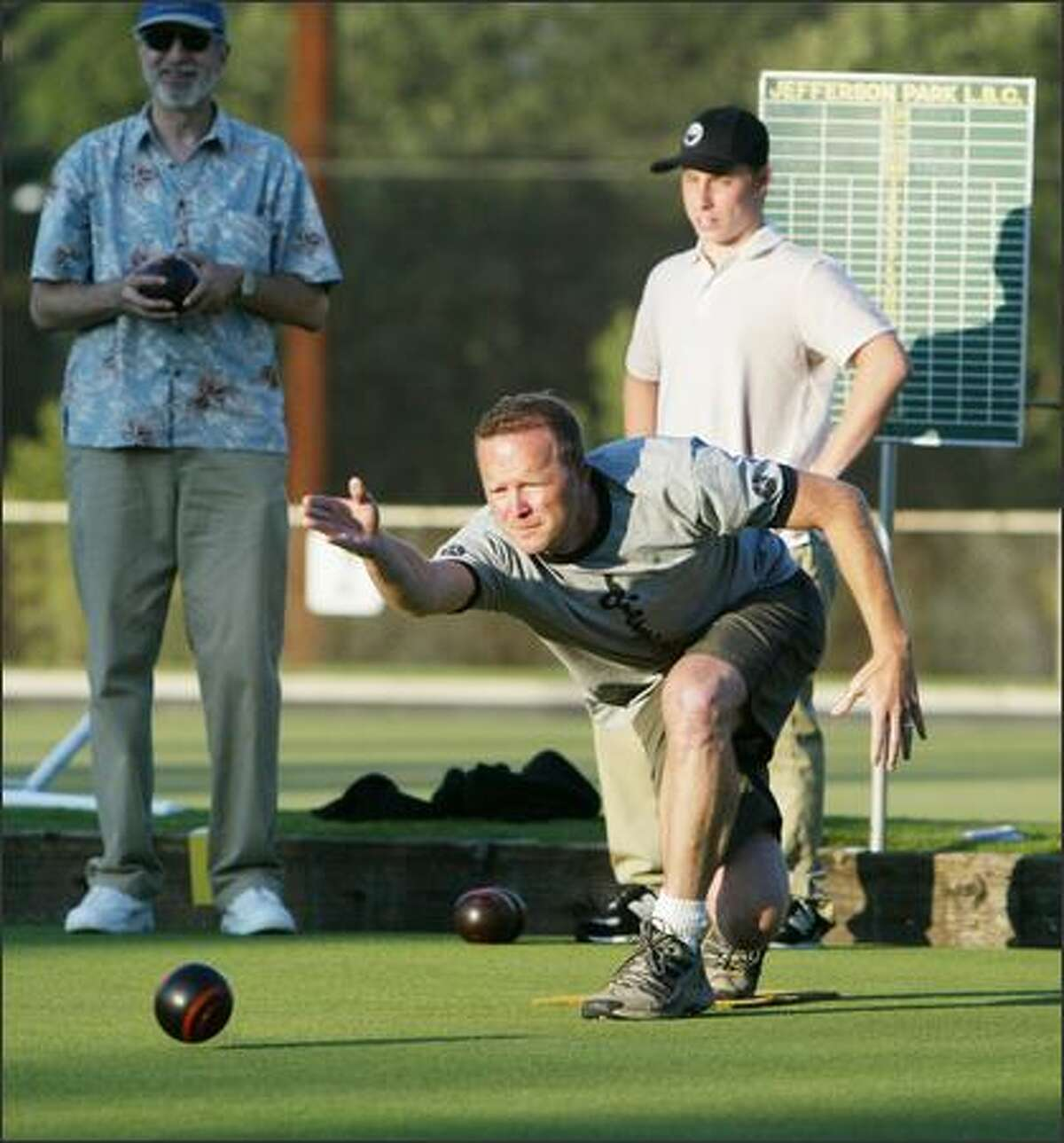 Pete Smith lets loose his bowl as Gene Freedman (left) and Harry Jamieson watch during an Aug. 2 match. Lawn Bowling is dying in the U.S. But at Jefferson Park Lawn Bowling Club on Beacon Hill in Seattle, the sport is making a comeback among younger folks, as evidenced by a men's lawn bowling league called Men With Big Bowls that competes on Tuesday nights. Jamieson, for example, is 17 and going into his senior year at Garfield High School.