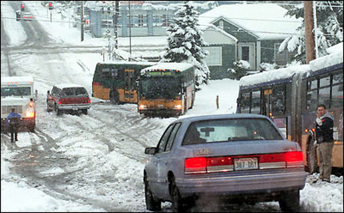 Overnight snowfall snarls traffic on Seattle streets. Here buses and motorists stall on a Northeast 75th Street hill just east of 25th Street, Northeast in Wedgewood.
