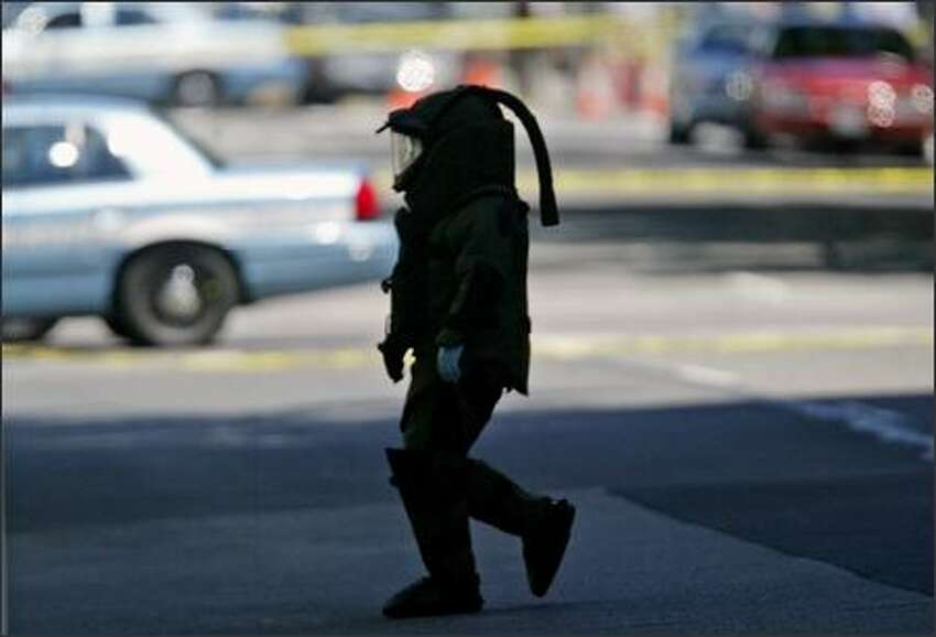 A Seattle Police Department bomb specialist approaches the courthouse.