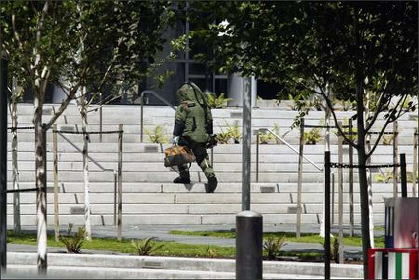 A bomb expert enters the federal courthouse in Seattle after a Seattle police officer shot and killed a man with a grenade.