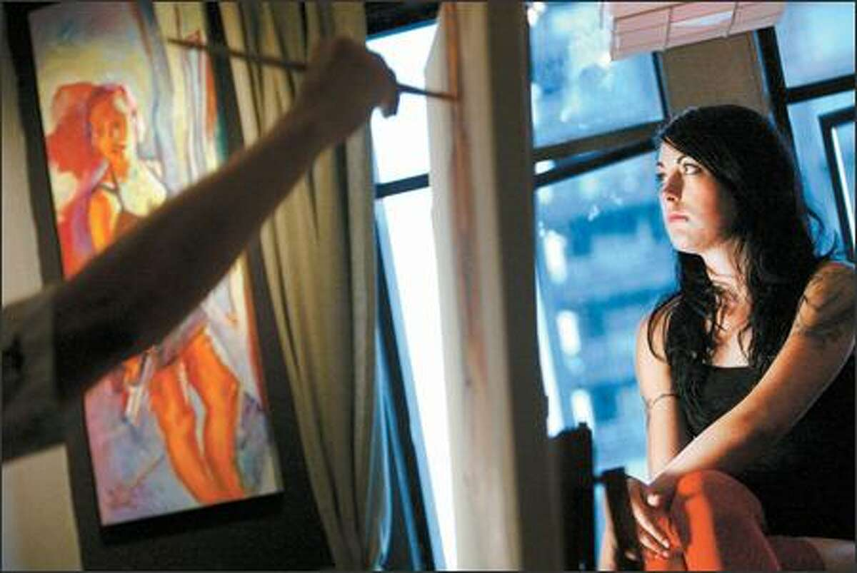 Ethan Jack Harrington works on a painting of model Veronica Nelson during a session at his apartment in Belltown, where the artist has become a neighborhood celebrity.