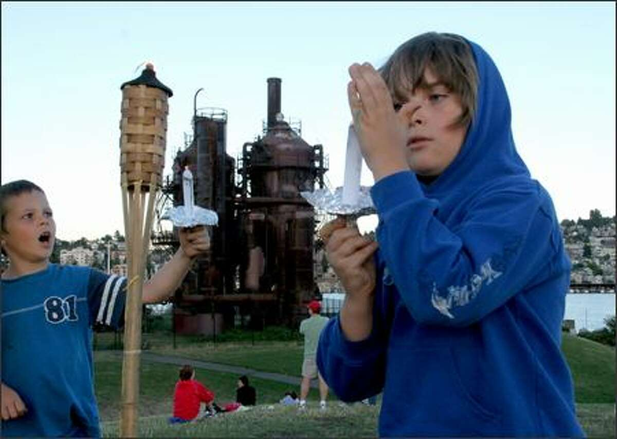 Sean Maguire, 8, and his brother Druce Maguire, 6, light candles on tiki torches at a vigil at Gas Works Park.