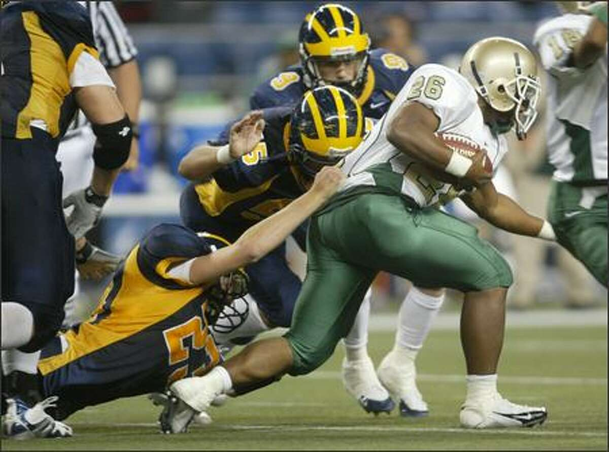 Bellevue's Jonathon Richards (23) grabs hold of Poly running back Troy Guthrie after a short gain in the second half.