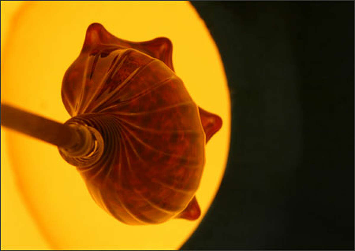 A glass conch shell glows in the furnace of Smith's workshop.