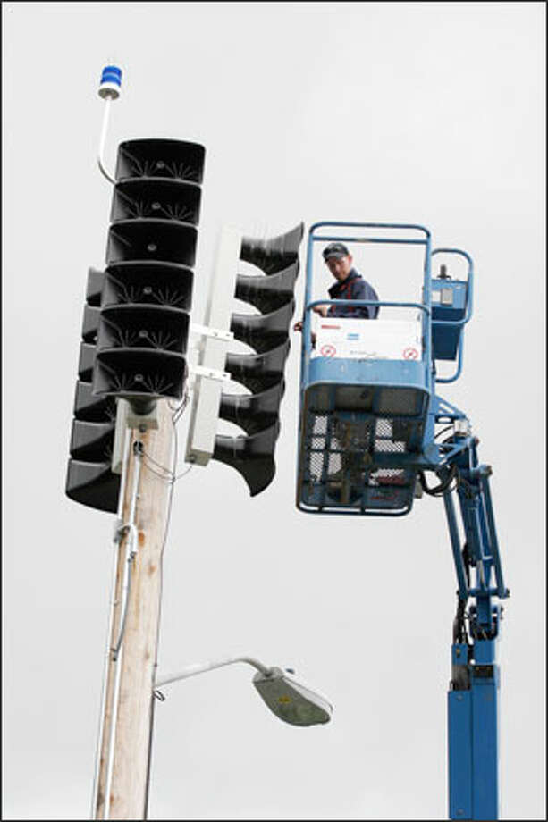 Merit Electric worker Brett Lineback of Spokane installs bird spikes on the new hazardous- warning speakers on Western Avenue yesterday. Photo: Meryl Schenker/Seattle Post-Intelligencer