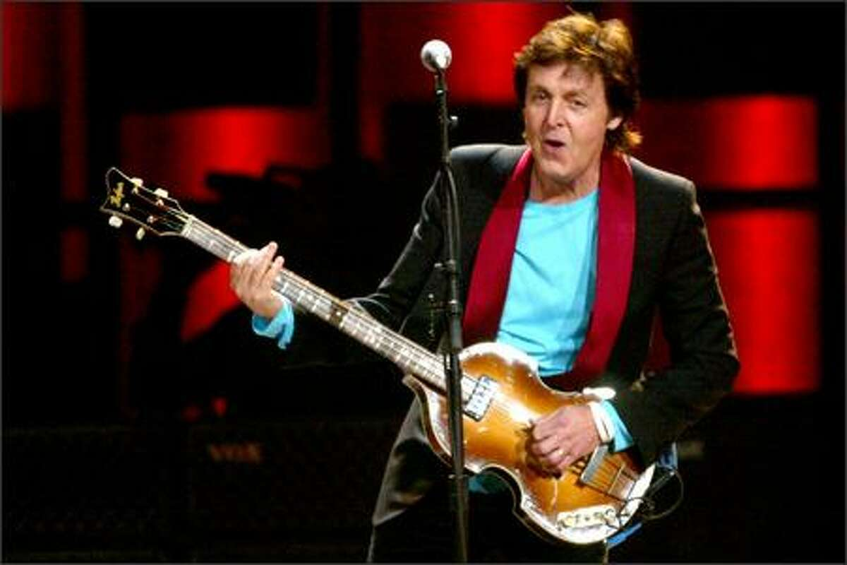 Wielding his trademark bass, Paul McCartney performs at the KeyArena on Thursday night. The ex-Beatle got the concert started with