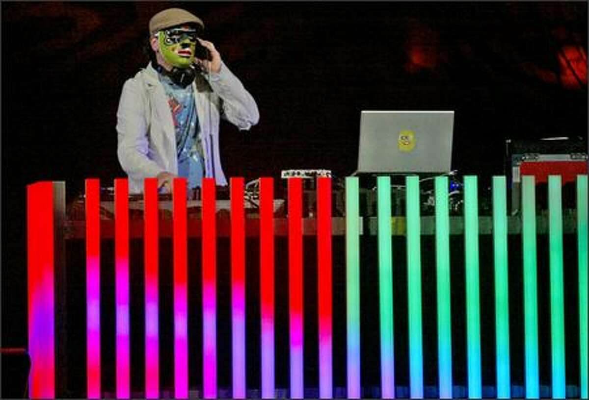 A DJ spins discs in sync with a video presentation before Paul McCartney and his band perform.