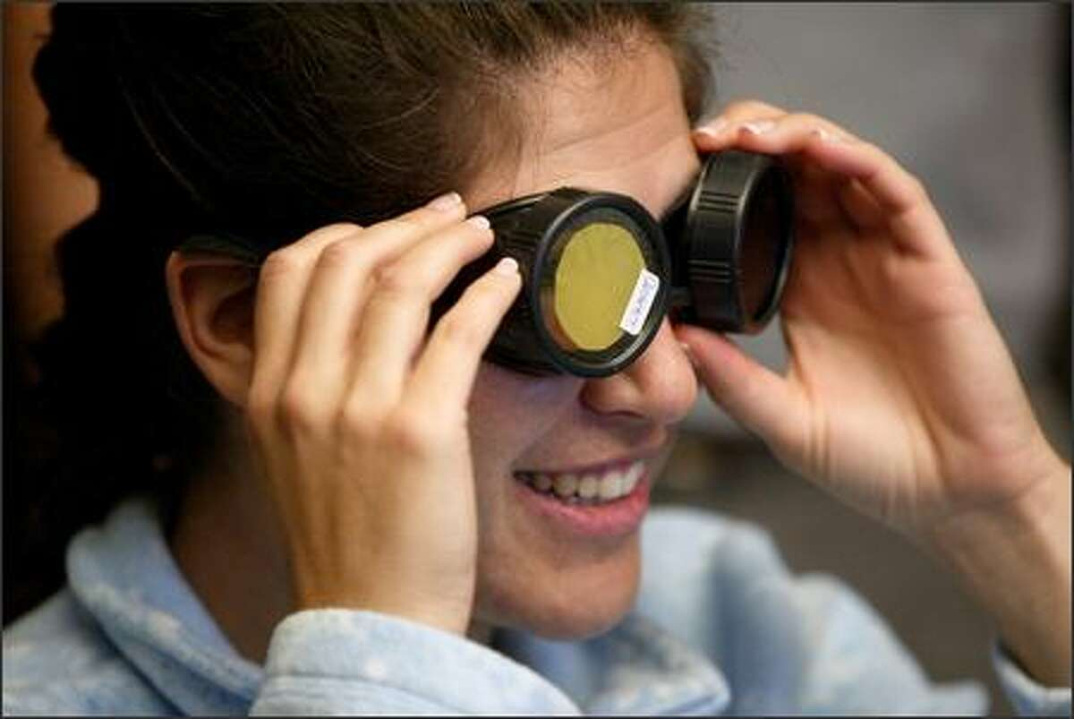 Prior to boarding the flight, Boeing engineer Bethany Franko tries on a pair of goggles used to simulate the vision of an elderly person with a cataract.
