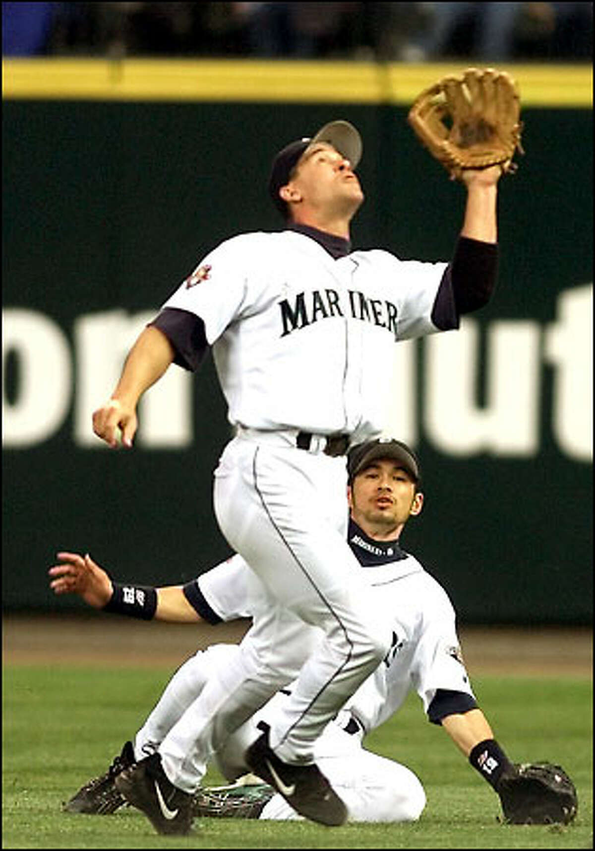 Ichiro Suzuki, below, barely avoids a collision with second baseman Bret Boone, who came down with the pop fly hit by Ryan Klesko in the sixth inning of Friday's game against San Diego.
