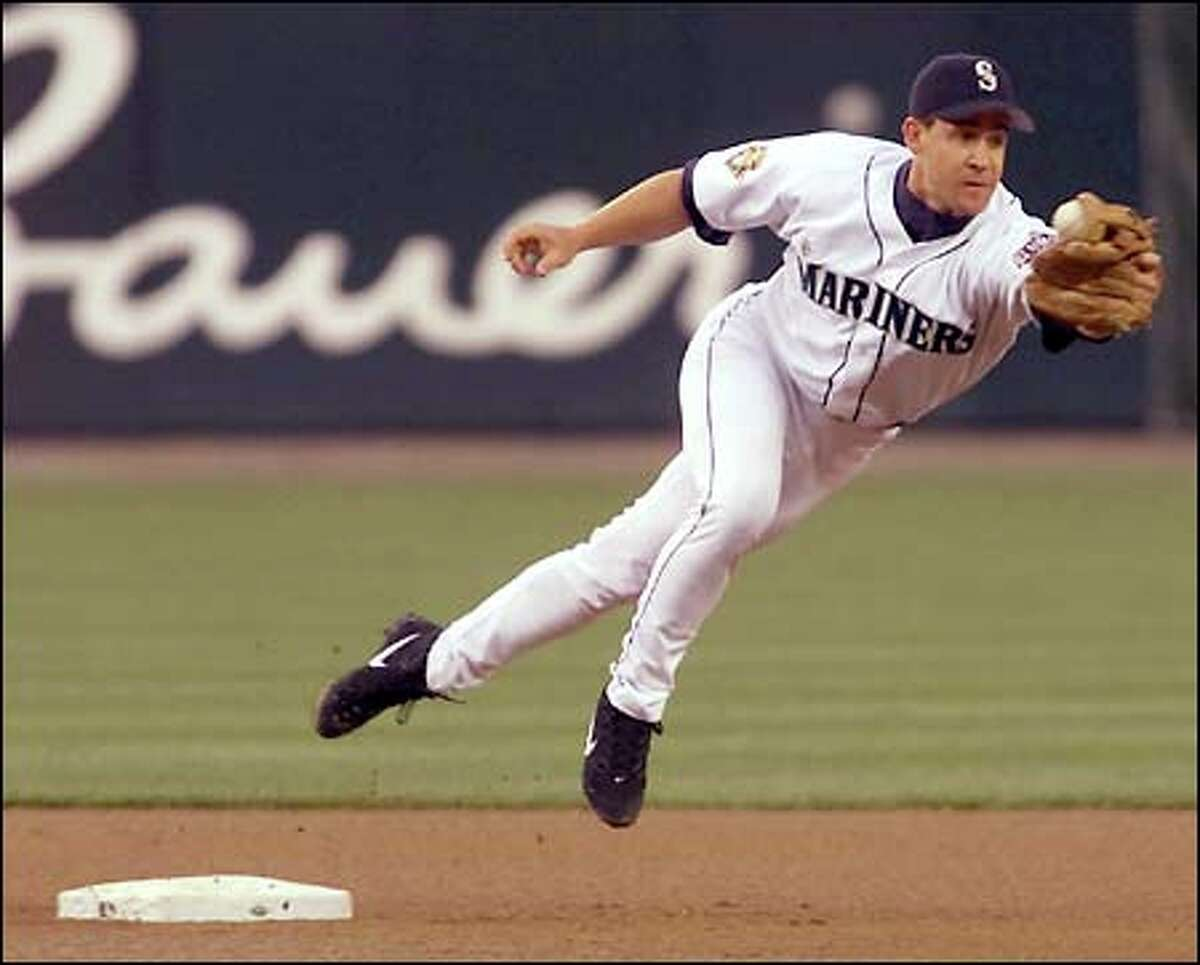 Mariners second baseman Bret Boone is pulled off the bag on a throwing error by third baseman David Bell in the fourth inning. The error helped the Giants score two unearned runs.