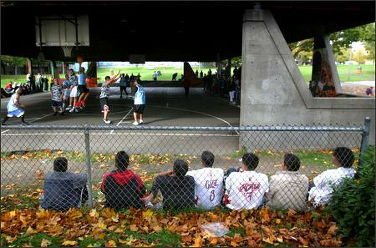 Players for Putla wait on the sidelines for their turn to compete in Seattle as the Lakers and Rio Balsas play on the court. Most of the Putla players are from Oaxaca, Mexico. Men from various Mexican states gather with their families and friends every Sunday for basketball at the park.