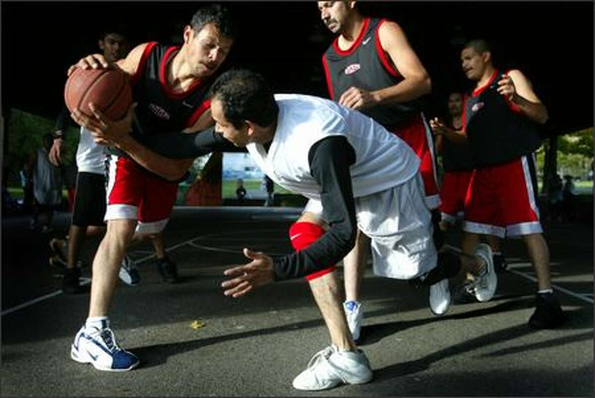 David Arroyo, center for Ya Sabes, reaches for the ball from Genaro Castanada, playing for Michoacan, during a basketball game. Both men are from Nayarit State in Mexico.