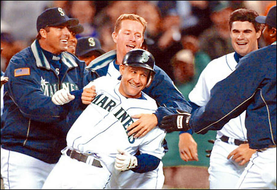 Bret Boone is mobbed by teammates following his game-winning single in the bottom of the ninth. The Mariners scored four times in the inning to erase a 6-3 Chicago lead. Photo: Associated Press