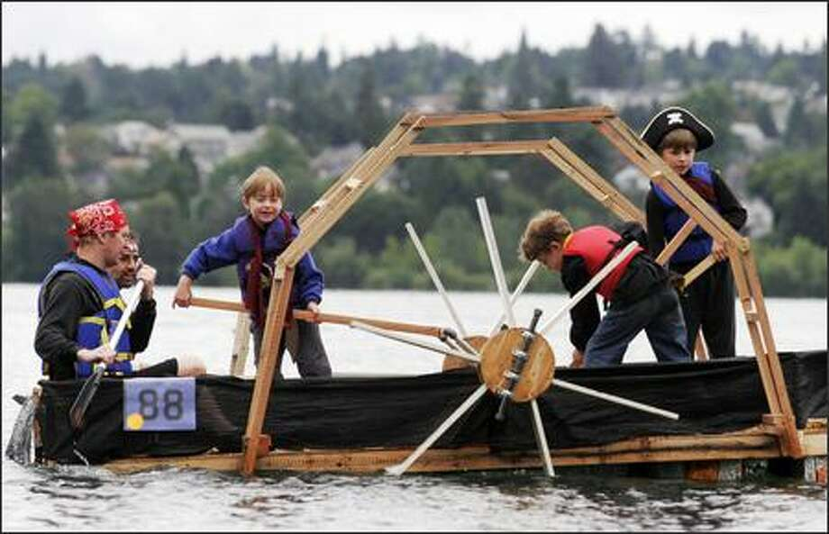 "Torben Christiansen, left, Richard Seroussi, left back, and their sons Andrew Christiansen, 7, left center, Daniel Seroussi, 8, right center, and Jacob Christiansen, 9, right, man the ""Pirates of the Cheese-Cutters"" milk carton float at the first day of Seafair's Milk Carton Derby at Green Lake. Photo: Niki Desautels, Seattle Post-Intelligencer"
