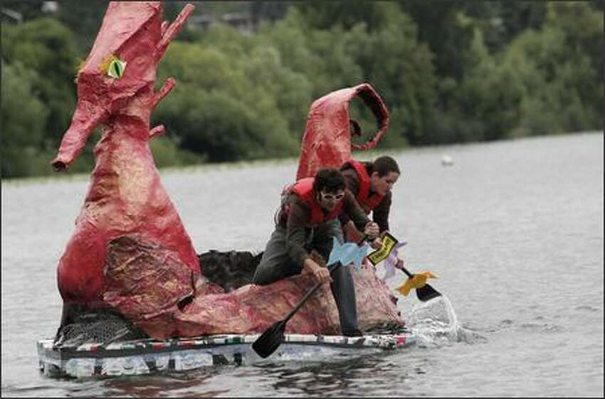 Gareth Mccammon, left, and Jennifer Lehnert, right, paddle towards the starting line for the '14 years and older' open race at the Seafair Milk Carton Derby in their Charlie and the Chocolate Factory inspired