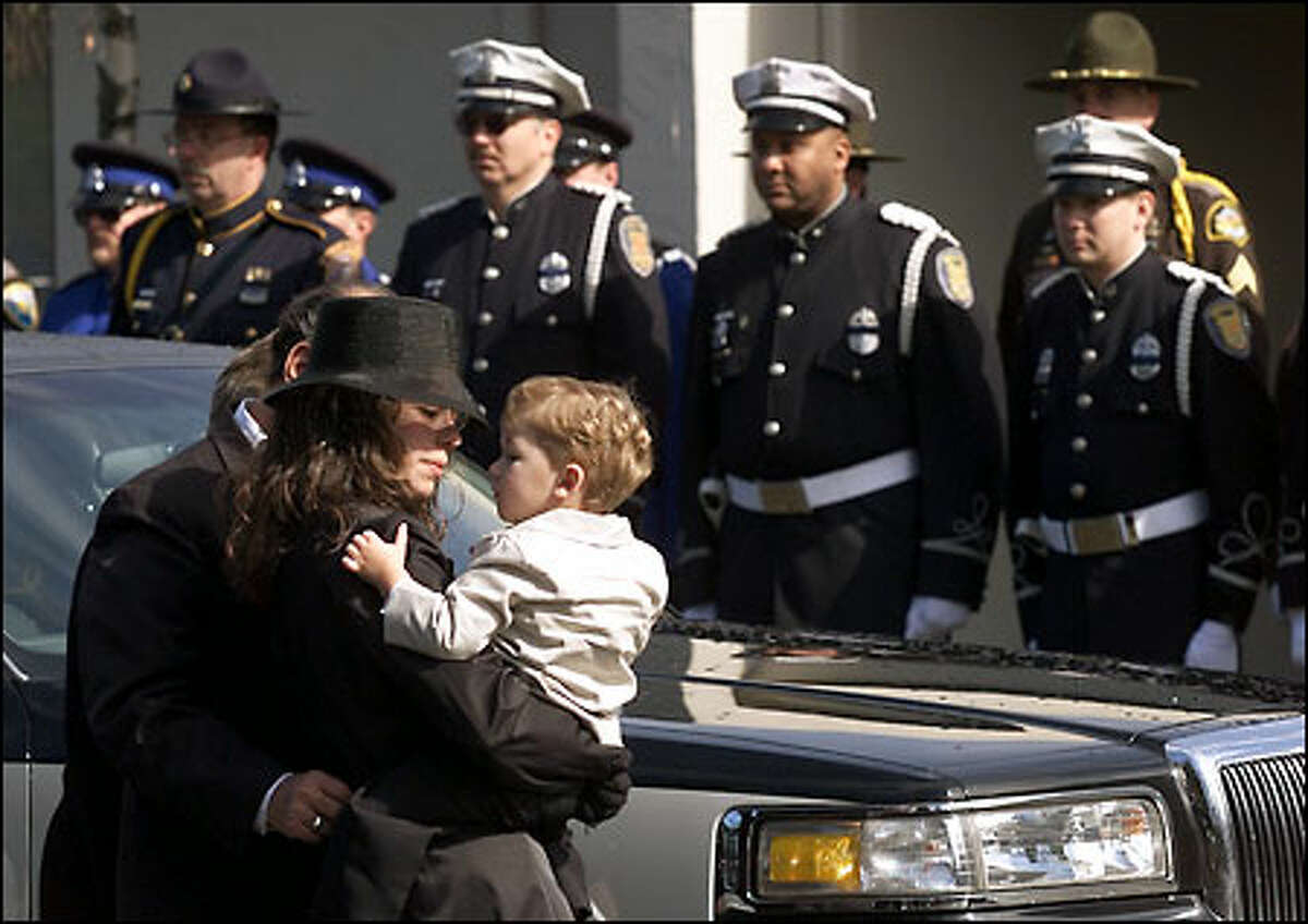 Officer Steven Underwood's widow, Rosathe, holds their 2-year-old son, Esteban, after arriving at the Christian Faith Center.