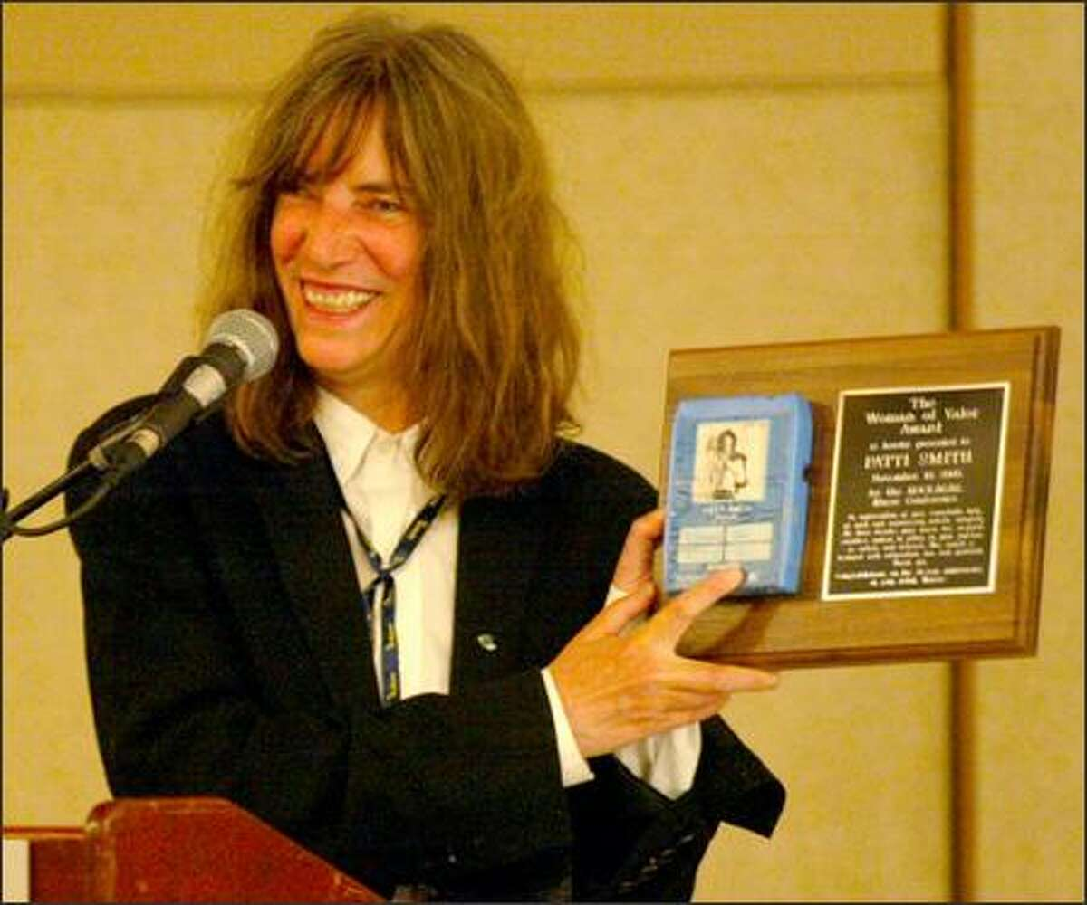 Patti Smith holds up her Woman of Valor Award to the audience. She explained that her father bought a cassette with her picture on the label and gave it to her.