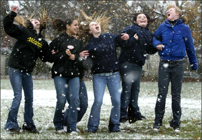 From left, Samantha Weyer, 14; Theresa Barnes, 13;, Torey Perfect, 13; Sarah Bach, 14; and Vanessa Burke, 14, leap as they try to catch snowflakes on their tongues at the Queen Anne Playfield as the white stuff made a rare visit to Seattle. Some McClure Middle School students were let out of class and gathered in the park to enjoy the weather.