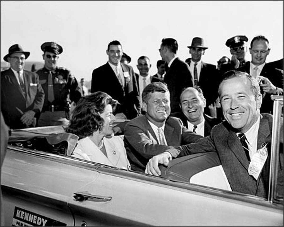Senator John F. Kennedy rode in a convertible during a campaign appearance in Seattle on September 6, 1960. Seated with the presidential candidate are Governor Albert D. Rosellini, Senator Henry M. Jackson and Kennedy's sister, Eunice Kennedy Shriver. The ribbon worn by Senator Jackson proclaims the visit to be an official Seafair event and welcomes the entourage to the University Plaza Hotel.