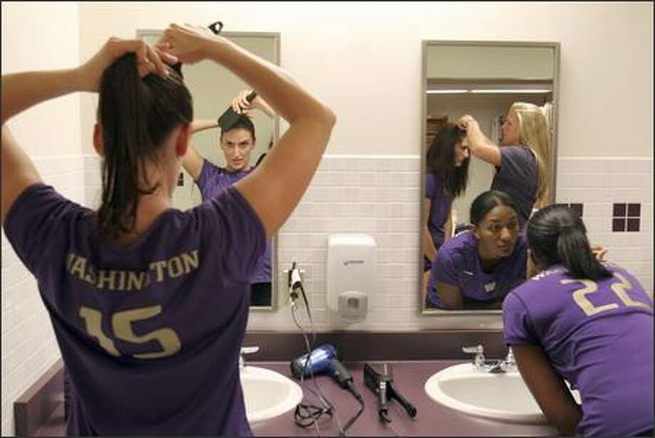 Danka Danicic, left, and Jill Collymore, right, get ready for a Fox Sports Network broadcast game against UCLA in their locker room at UW. In the mirror are seniors Brie Hagerty, left, and Jessica Veris, right. Danicic is a defensive specialist from Serbia & Montenegro. Photo: Meryl Schenker, Seattle Post-Intelligencer