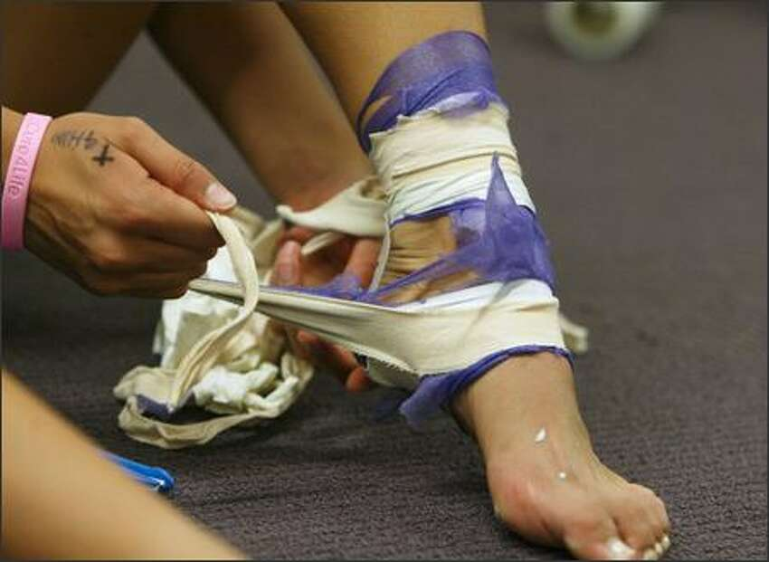 Candace Lee unwraps her taped ankle after UW beat the UCLA Bruins 3-0 in Seattle on October 13, 2005.