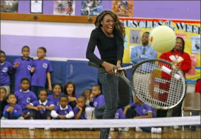 Venus Williams plays tennis with a giant-sized tennis racquet at T.T. Minor Elementary School in Seattle. The Williams sisters are visiting Seattle as part of a three-city tour.