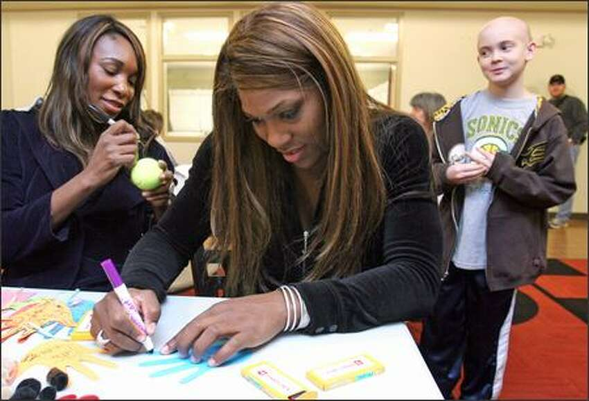 Venus Williams, left, signs a tennis ball for Michael Lavin, 11, of Kalispell, Mont., who is staying at Ronald McDonald House with his family while being treated at Children's Hospital in Seattle. Serena Williams, center, decorates a paper hand that she will hang on the house's Christmas tree. The Williams sisters are visting Seattle as part of a three-city tour.