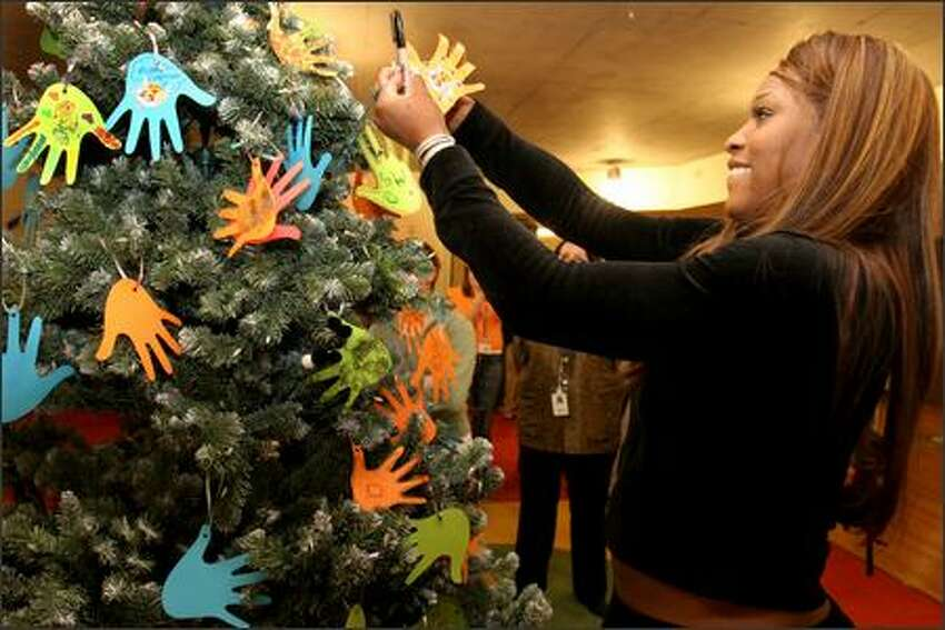 Serena Williams hangs a paper hand that she decorated on the Christmas tree at Ronald McDonald House in Seattle. The Williams sisters are visting Seattle as part of a three-city tour. Part of the proceeds from the tour benefit Ronald McDonald House Charities. The Seattle Ronald McDonald house can provide up to 80 families whose children are being treated at Children's Hospital.