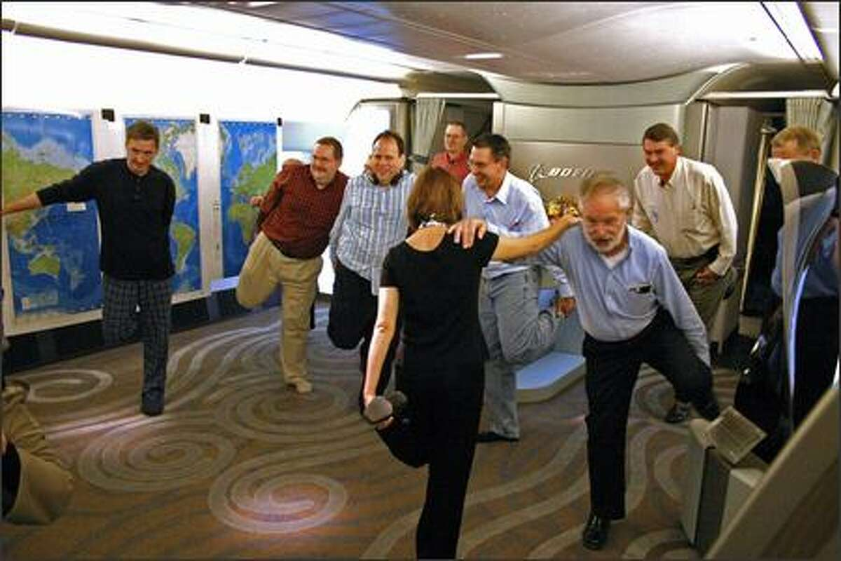 Flight attendant Maureen Walker leads some passengers in stretching exercises during the long flight. Holdng on to her is Don Philips, aerospace writer for the International Herald Tribune. The front cabin of the jet was empty of seats on this trip, leaving a large area for passengers to gather, talk and eat.