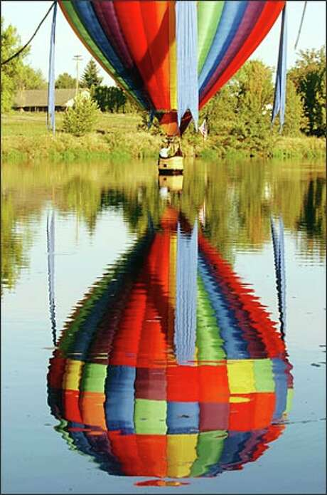 A hot-air balloon swoops low over the Yakima River when several dozen of the balloons were in Prosser for the 16th annual Prosser Balloon Rally in late September.Larsen: Fortunately, the wind let up long enough for some of the hot air balloons to skim the Yakima River in Prosser. Photo: Jeff Larsen, Seattle Post-Intelligencer