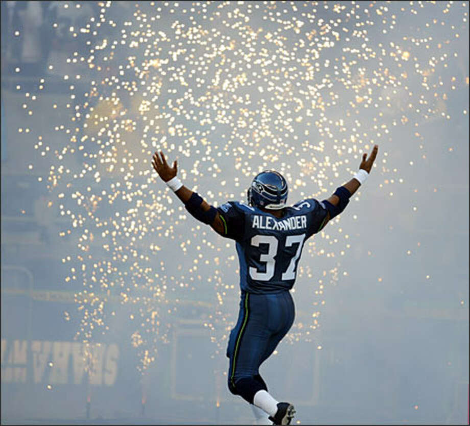 "Accompanied by fireworks, Shaun Alexander encourages the crowd at Qwest Field to cheer as he is introduced before the Seahawks' game against the Atlanta Falcons.Haller:The other day I saw a football photo in the P-I that I thought, at first glance, was my picture. Turned out that it was shot by an AP photographer. I realized that I've shot too many photos of tackles, catches, long passes, spectacular runs and sideline features, yet I still picked a football photograph as one of my favorites. This image makes me feel like Alexander had just thrown the sparkles into the air like it's special Seahawks ""pixy dust."" Whatever it was, it foretold of a magic spell he would bring to this season. Photo: Grant M. Haller, Seattle Post-Intelligencer"