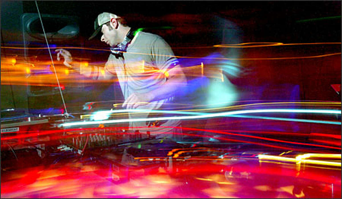 A swirl of sound -- represented by special camera effects -- wraps DJ Joshua James during the Spin-Off contest at Seattle's Element club. James, a finalist, lets the crowd's energy inspire his playlist. Haller: For those of you who have never watched a DJ, you should know that they don't just sit there and play CDs. They are constantly moving back and forth between two or more turntables, a couple CD players, working a sound board, running a light show and trying to keep up some form of communication with the dancers in front of him. I wanted to convey this frenzy with a slow shutter speed, panning and selective lighting on Joshua James at Element.