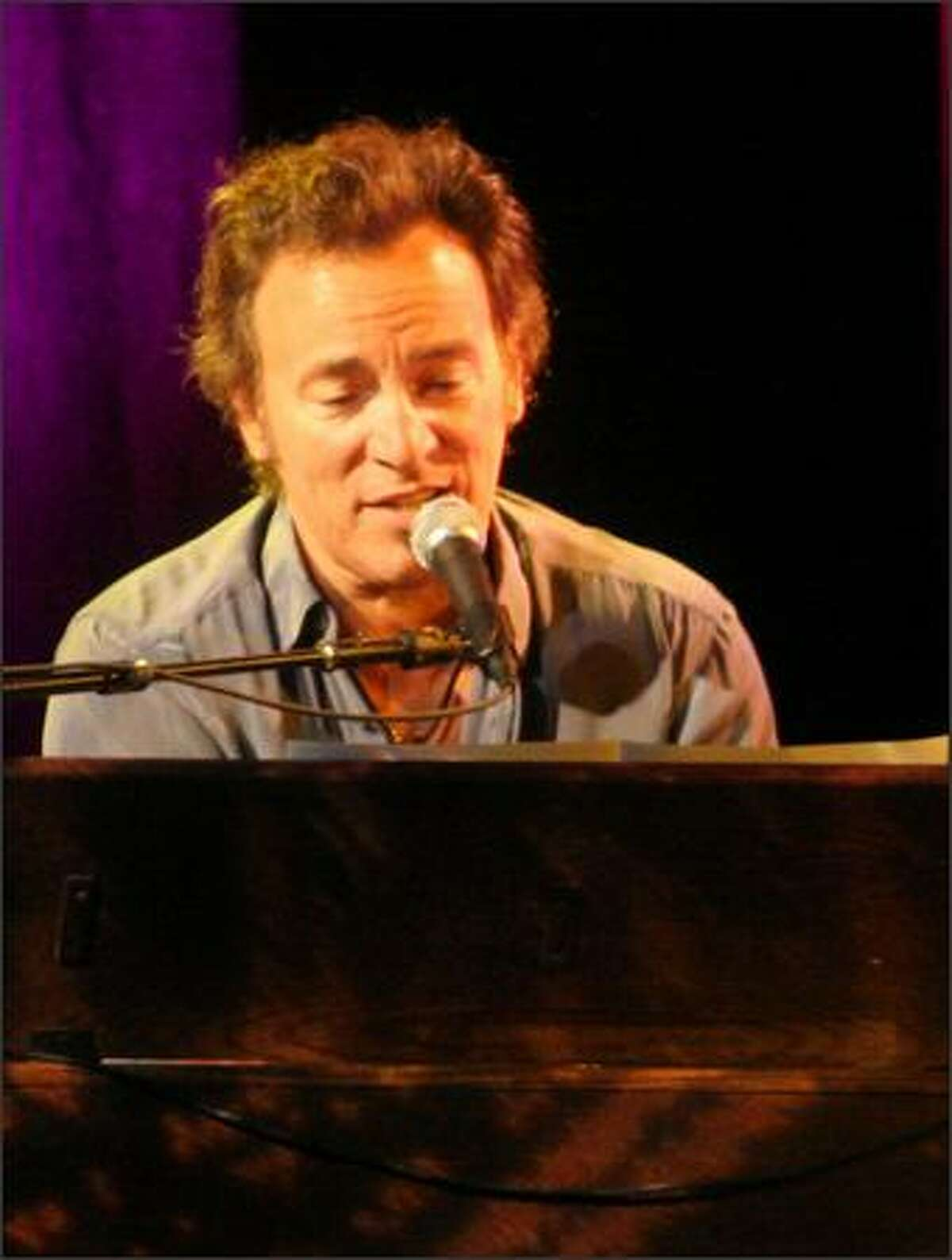 Bruce Springsteen works the keyboard to open the show with