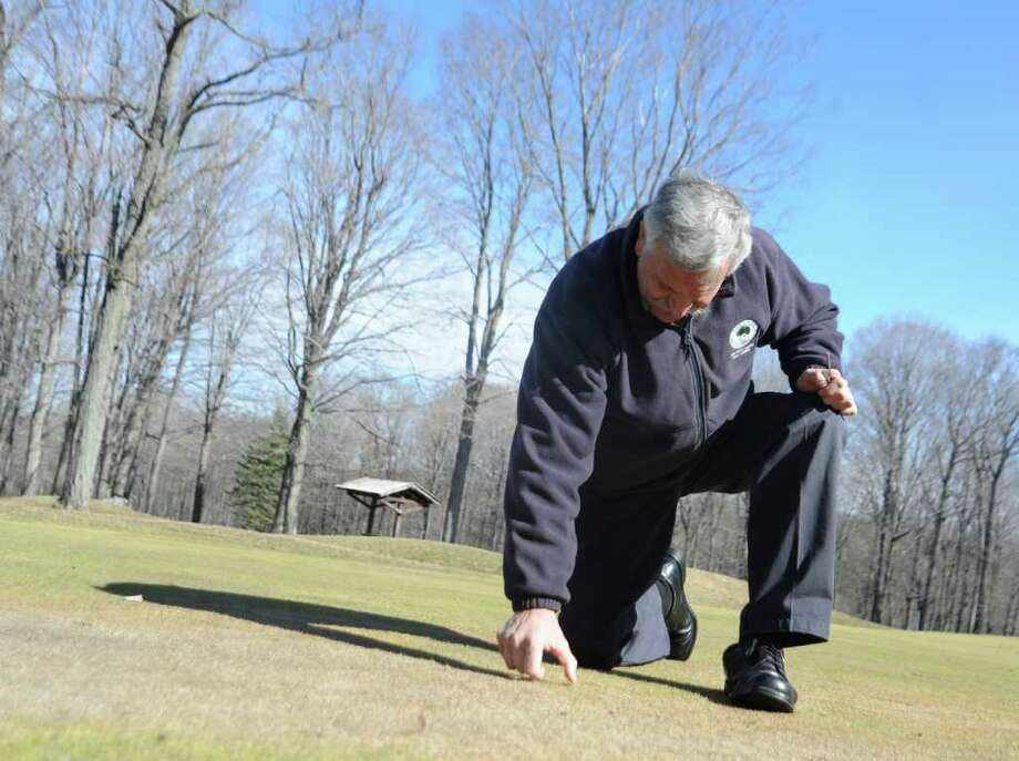David D'Andrea, operations manager at Griffith E. Harris Golf Course, looks at gray snow mold on the course on Thursday, March 17, 2011. Photo: Helen Neafsey / Greenwich Time