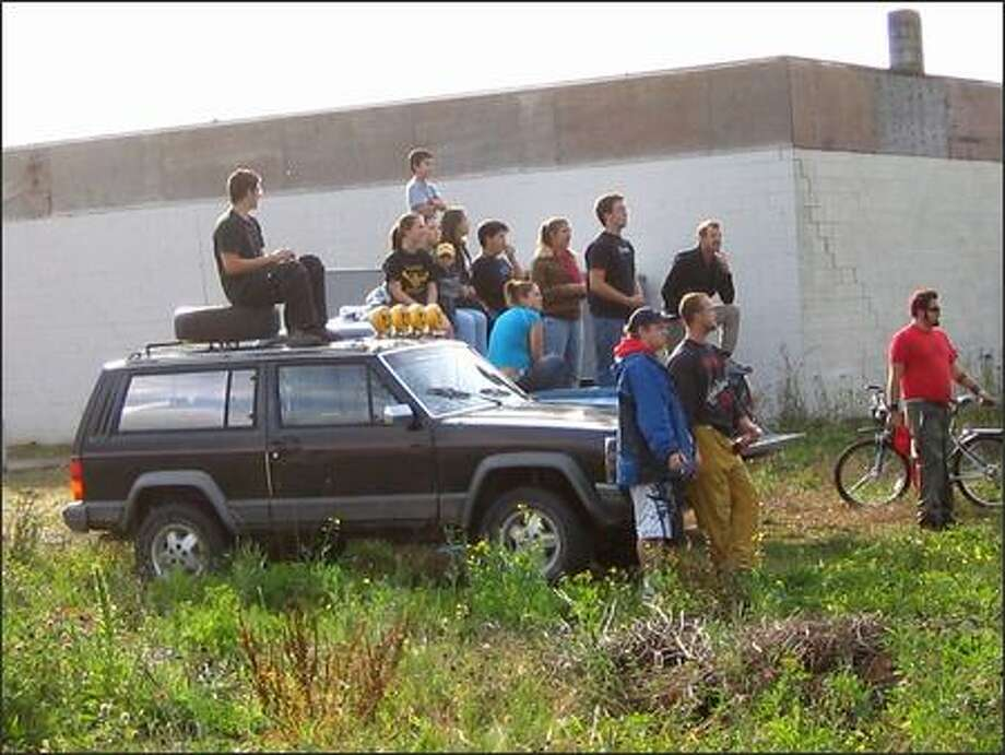 Agassiz townsfolk gathered in an empty lot near the train tracks waiting for some Magneto action. Photo: Athima Chansanchai, Seattle Post-Intelligencer