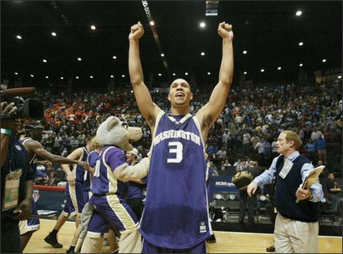 The UW's Brandon Roy raises his arms in victory toward the Husky fans following the University of Washington's 67-64 win over Illinois in the second round of the NCAA Men's Basketball Tournament at Cox Arena on the campus of San Deigo State University.