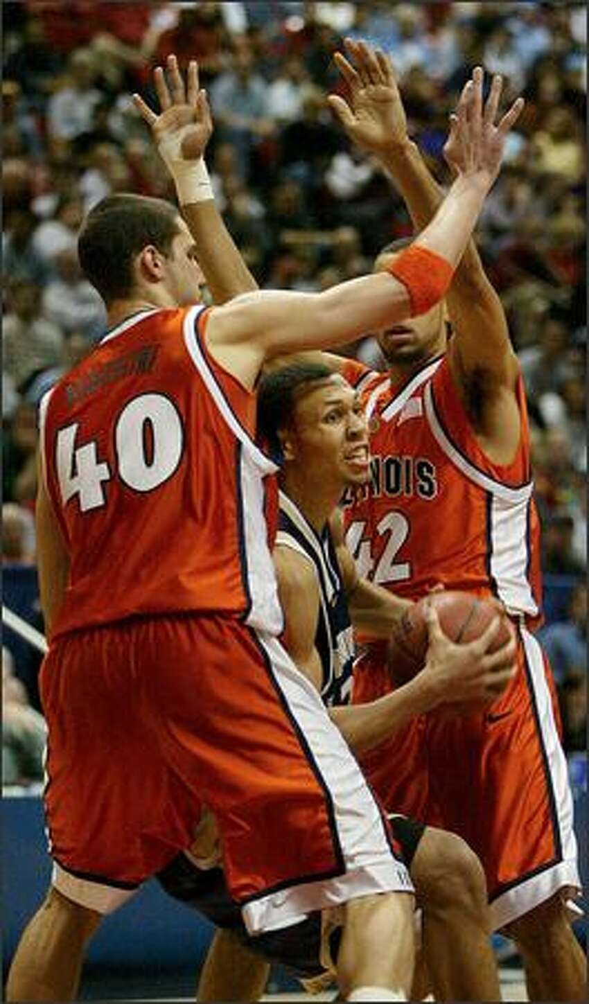 UW's Brandon Roy drives between Illinois' James Augustine (40) and Brian Randle to score two of his game high 21 points, and tie the score at 60 late in the second half.