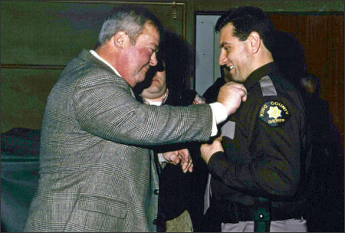 Joseph Pellegrini has his badge pinned on by his father, Vincent, a former deputy himself, at his police academy graduation in 2000. Pellegrini says he was