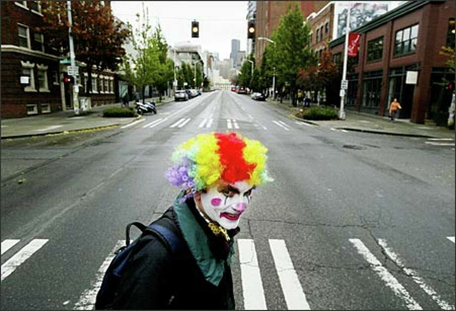 Sporting a clown face for Halloween, Larry Hohm, 49, of Seattle adds color to a gray Monday morning as he crosses Second Avenue on his way to work in Belltown.  Photo: Dan DeLong, Seattle Post-Intelligencer