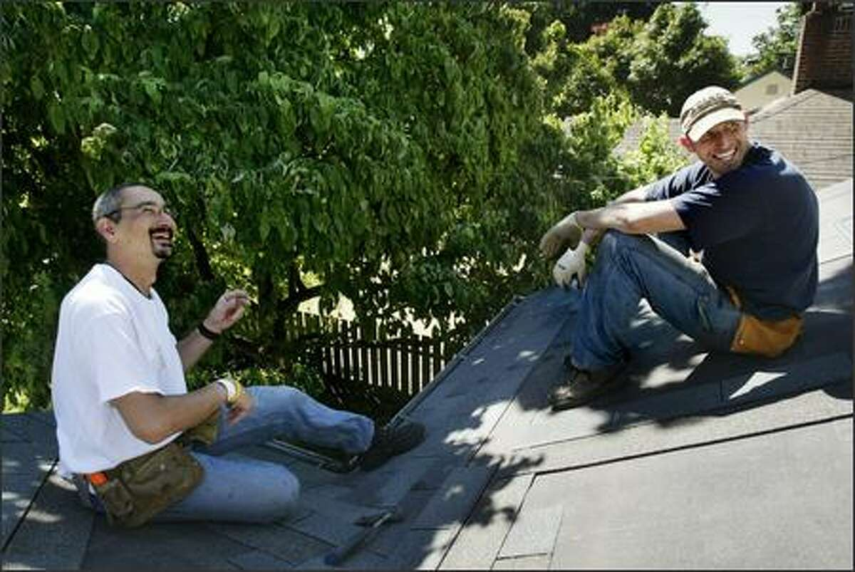 Greg Lipski, left, laughs with friends Tom Knapton, right, and Matt Kanaly, not pictured, on the roof of Knapton's Northgate-area home on July 29, 2005. Lipski, who has roofing experience, was showing his friends how to roof the house. The work helps take his mind off his cancer treatment.