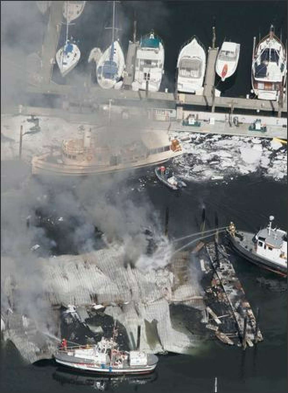 Firefighters work to control a fire at the Harborview Marina in Gig Harbor. More than 50 boats burned in the blaze.