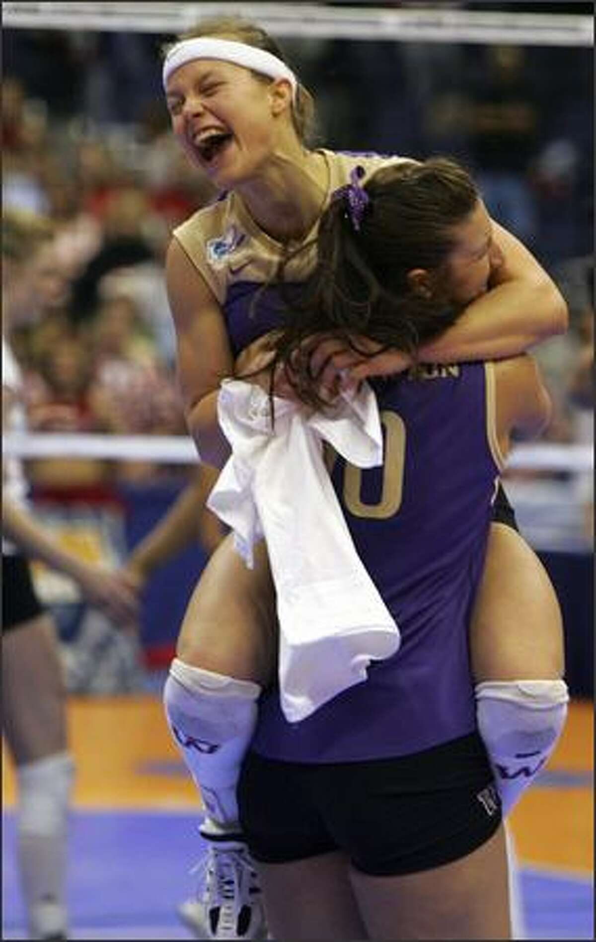 Courtney Thompson jumps into the arms of teammate Brie Hagerty after the Huskies won the national volleyball title.