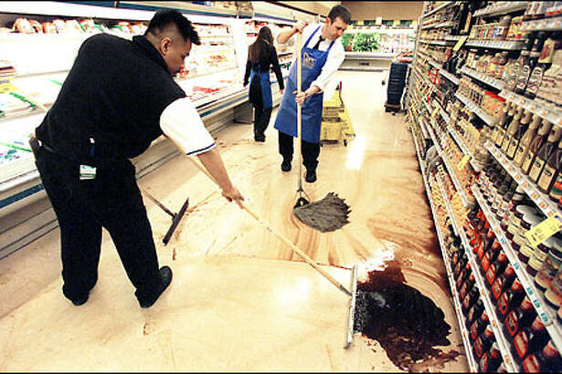 The quake caused bottles to fall off the shelves at the QFC grocery store on Broadway Avenue East at Harrison Street in Seattle. Employees Keoni Cadavona, left, and Steve Cantin help clean up the mess.