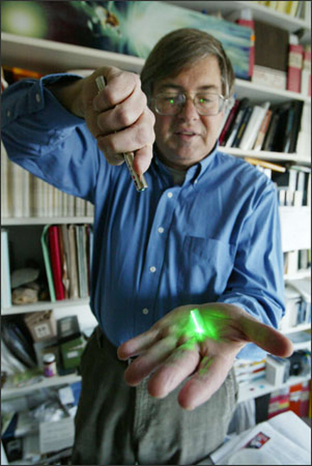 UW astronomer and Stardust lead scientist Don Brownlee illuminates, with a laser pen, a material called aerogel, a superlight glass foam used on Stardust to collect cosmic dust.