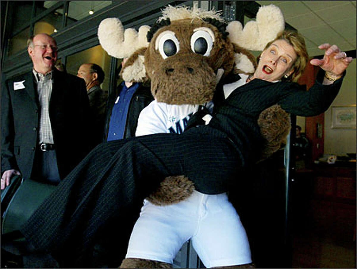 When the Mariner Moose asked Gregoire on Opening Day to put down her coffee, she had no idea he was planning to pick her up. The surprised governor was a good sport about it.Schenker: Gregoire jokingly wanted to know where her security detail was when this occured. Things had been extremely quiet in the owners box up until the moose arrived. Everyone was quite sure there would be no picture to make except for politicians hobnobbing, and they were surprised when I came back with this.