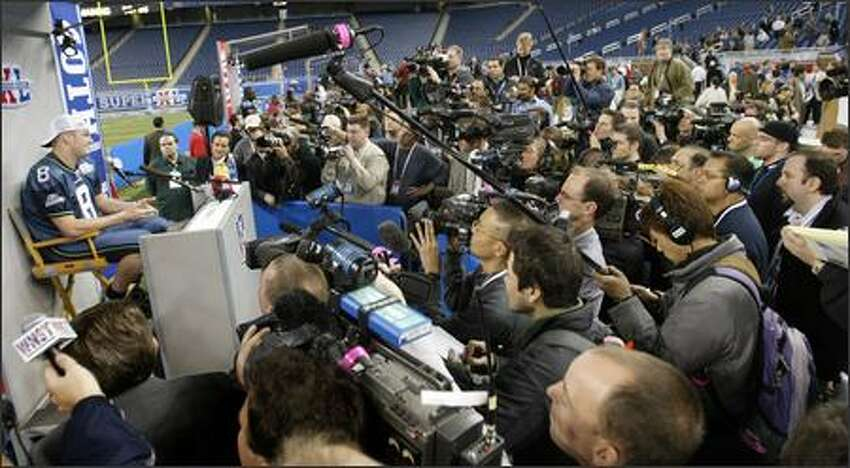 Matt Hasselbeck reads the Media Day coverage as a crowd, including P-I editorial cartoonist David Horsey (tallest man at rear center) looks on.