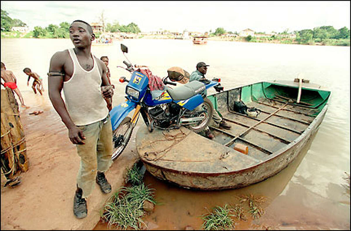 A ferryman waits for passengers on the Gambia River across from Basse Santa Su. For about a dollar, he will transport a traveler, a motorcycle and livestock across the river.