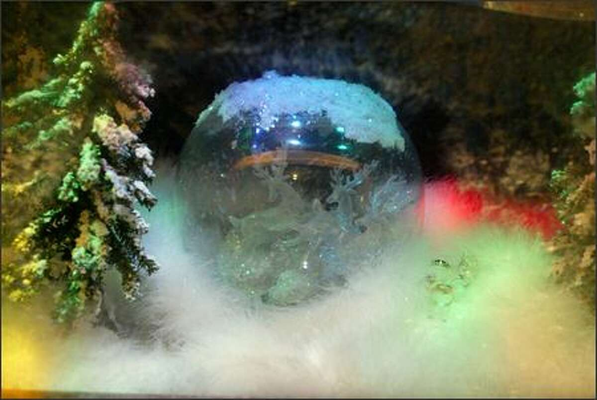 A snow globe, diamonds and a white feather boa make a happy winter scene in Goldmine Jewelry's miniature picture windows at 1405 First Avenue in downtown Seattle.