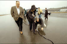 FEMA Director Joe Allbaugh, left, Sen. Maria Cantwell and Rep. Brian Baird check out a large crack in the runway at the King County Airport.