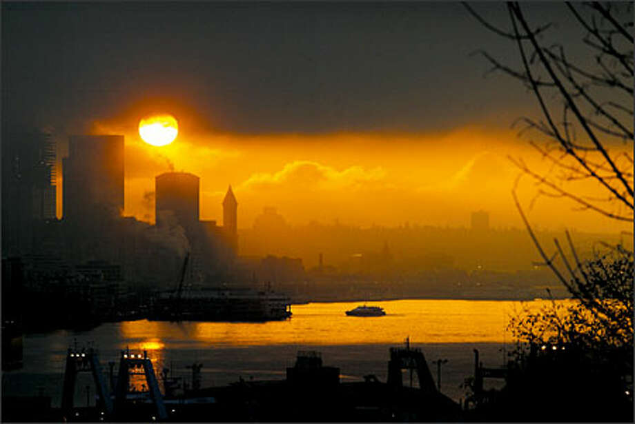 The sun rises over Seattle's Elliott Bay.Webber:I took this photo on my way to work around 7:30 a.m. I was coming over the edge of Magnolia Bluff and the sun was shining through the clouds, reflected on the water. I found a place to park and I got out my camera and did what I was supposed to do -- even though I wasn't on the clock. Photo: Phil H. Webber, Seattle Post-Intelligencer